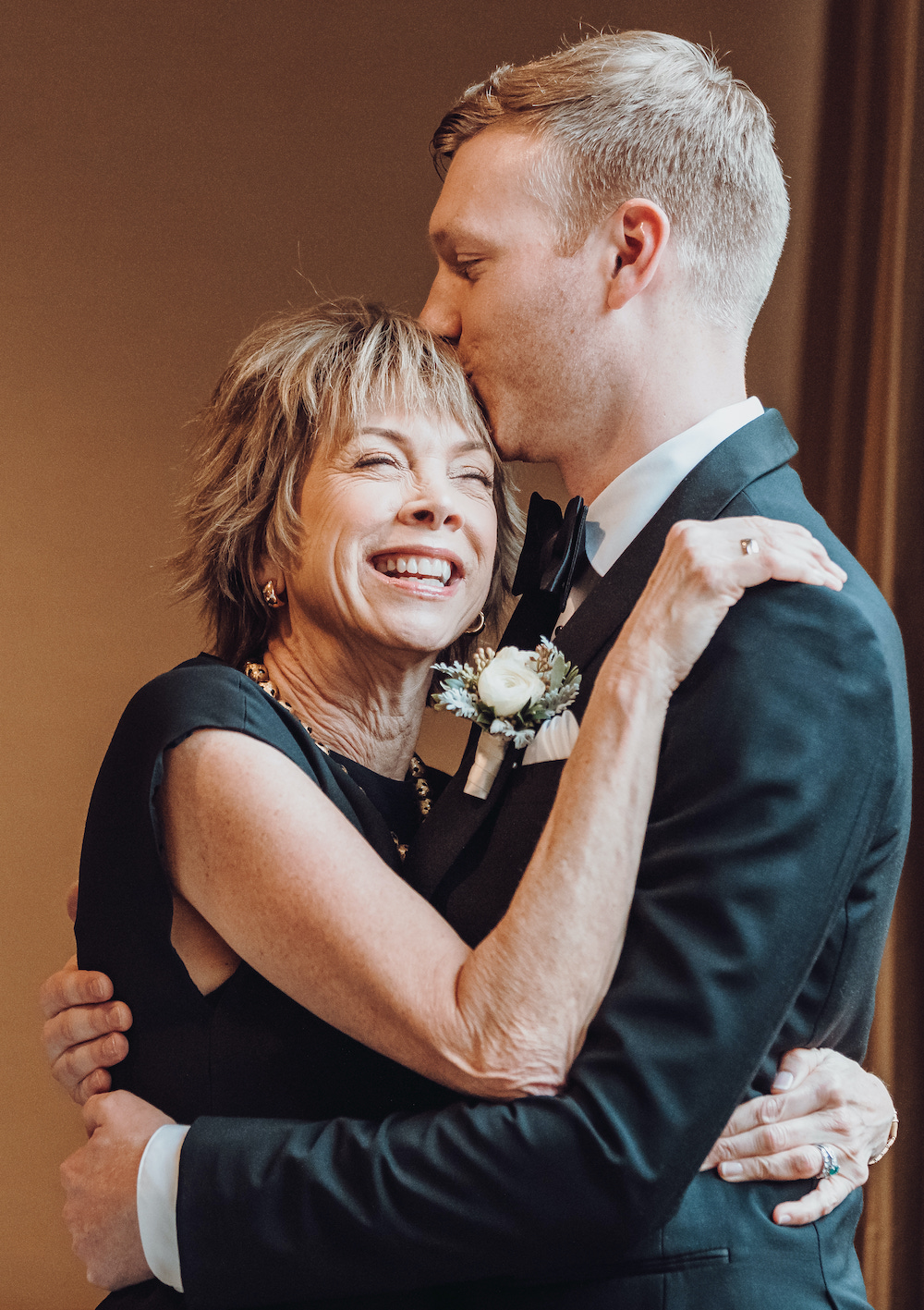 Groom in black tuxedo embracing his mother as they laugh.