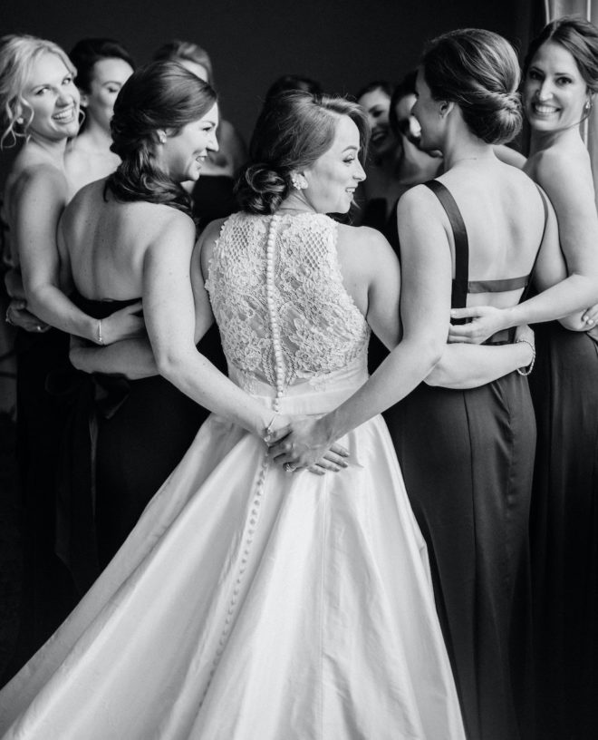 Black and white photograph of bride, wearing long white gown with lace back, hugging group of bridesmaids in various updos wearing sleeveless black silky gowns.