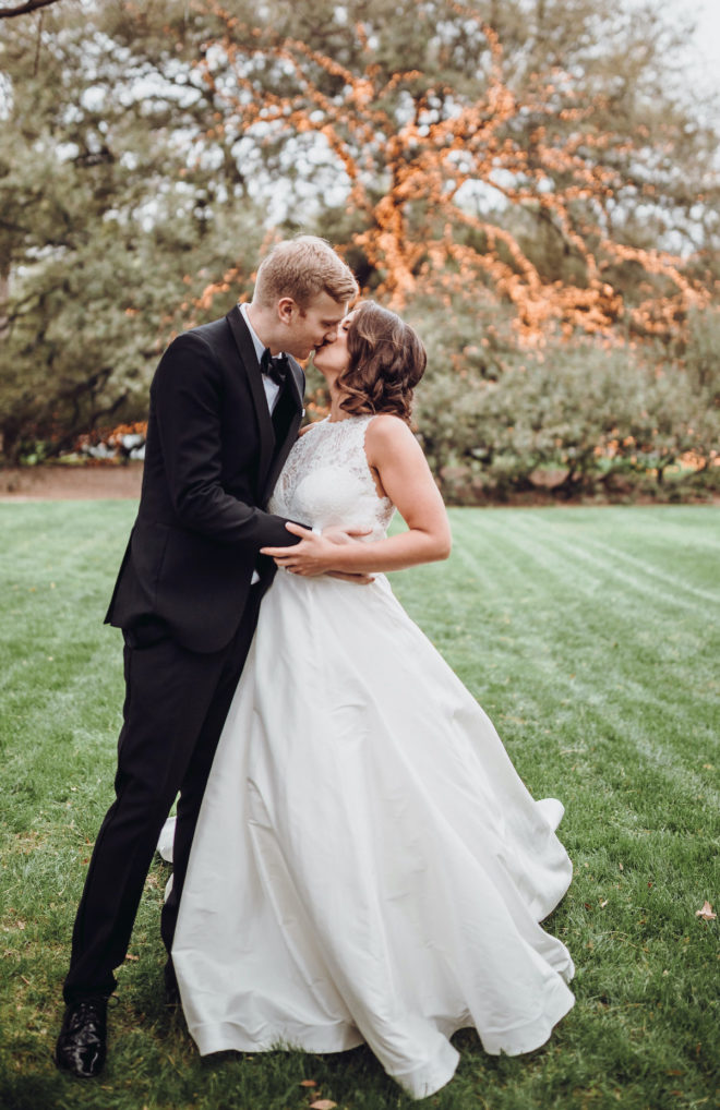 Groom, in black tuxedo and bowtie, kissing bride, in white sleeveless princess cut gown, in front of large Oak tree covered in string lights at the Houstonian Hotel Club and Spa.
