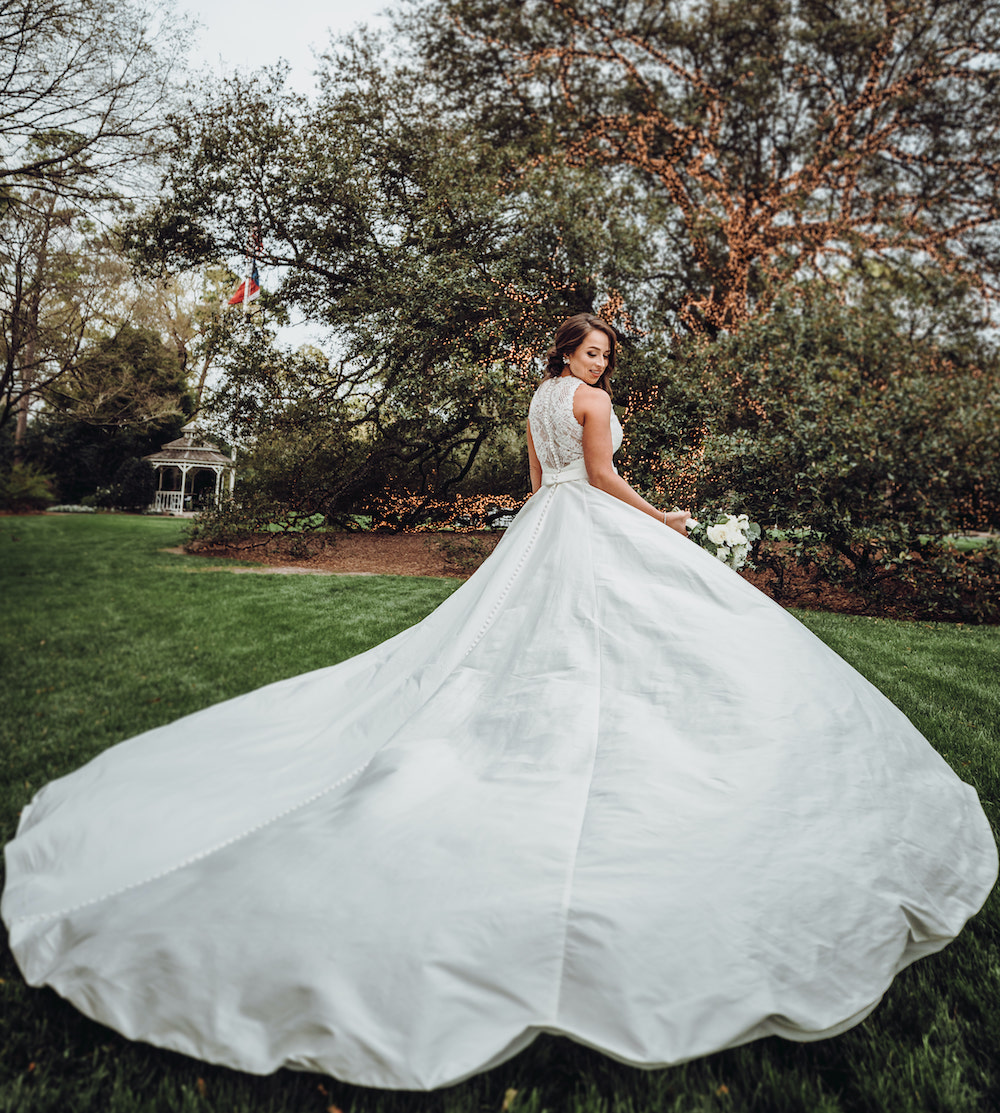Bride shows off the back of her wedding gown showcasing the impressive train and lace back details.