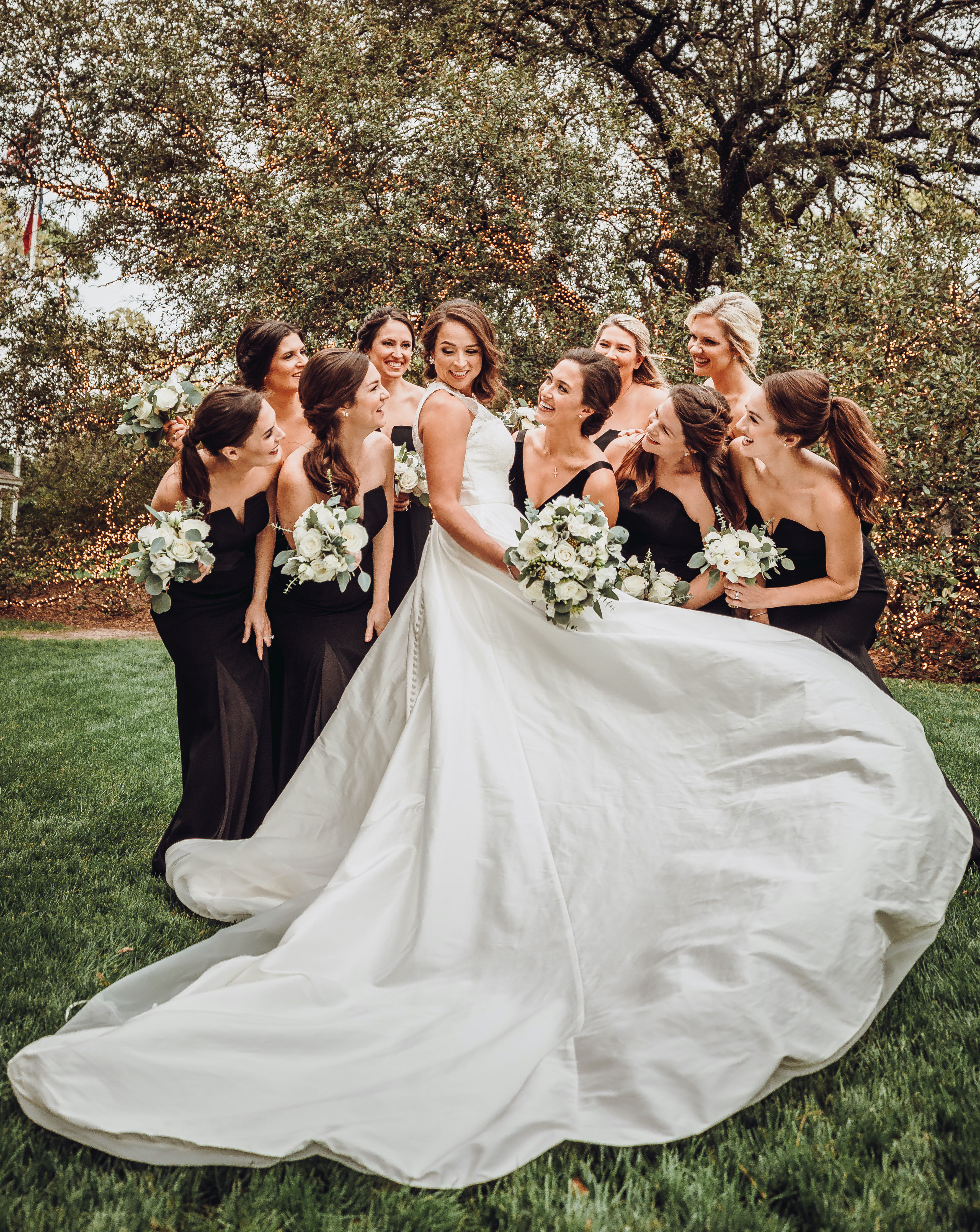 Bride showing off long, elegant wedding gown train as bridesmaids dressed in black admire and smile.