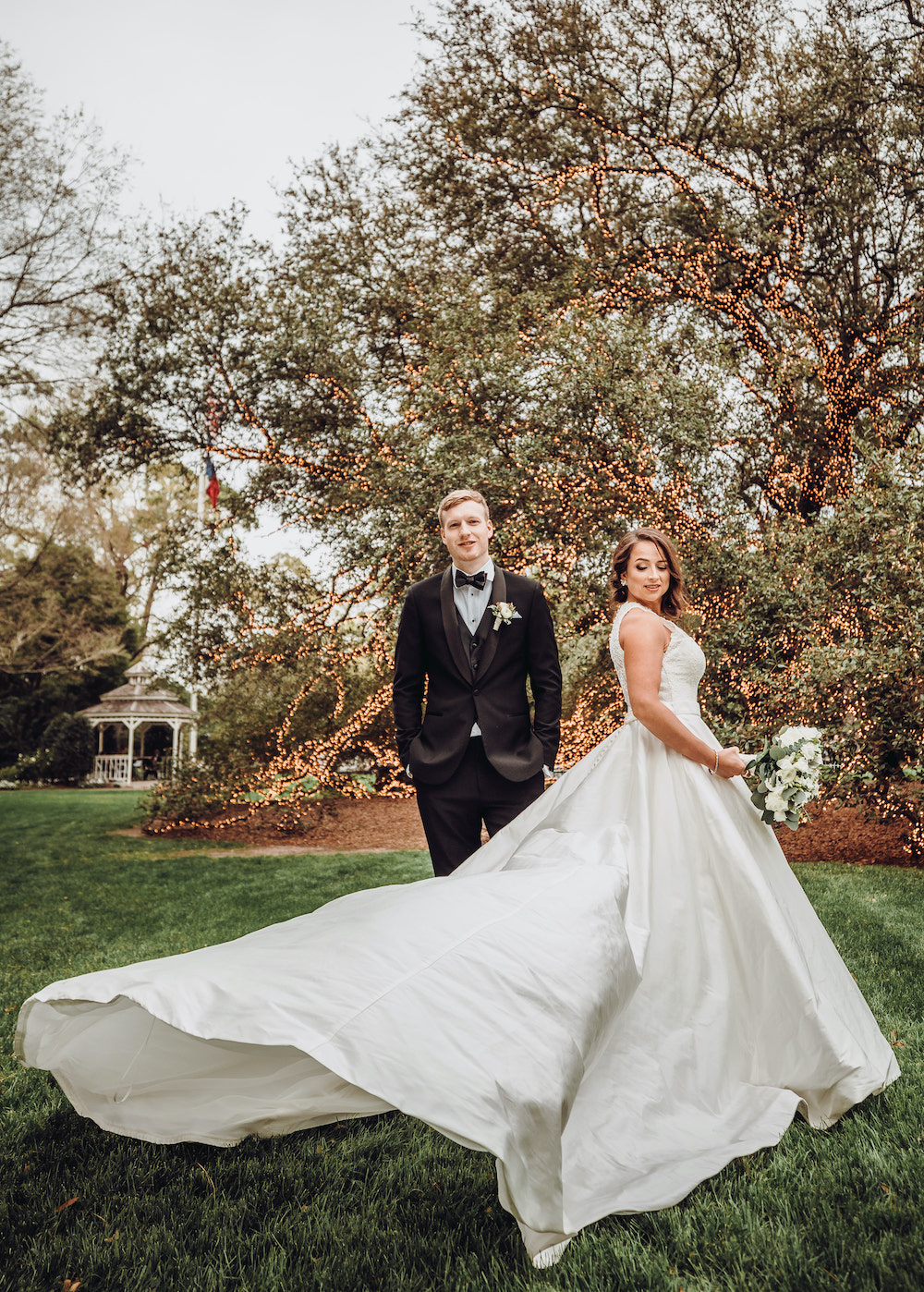 Bride wearing an elegant wedding gown and groom in black tuxedo posed in front of The Houstonian live oak tree
