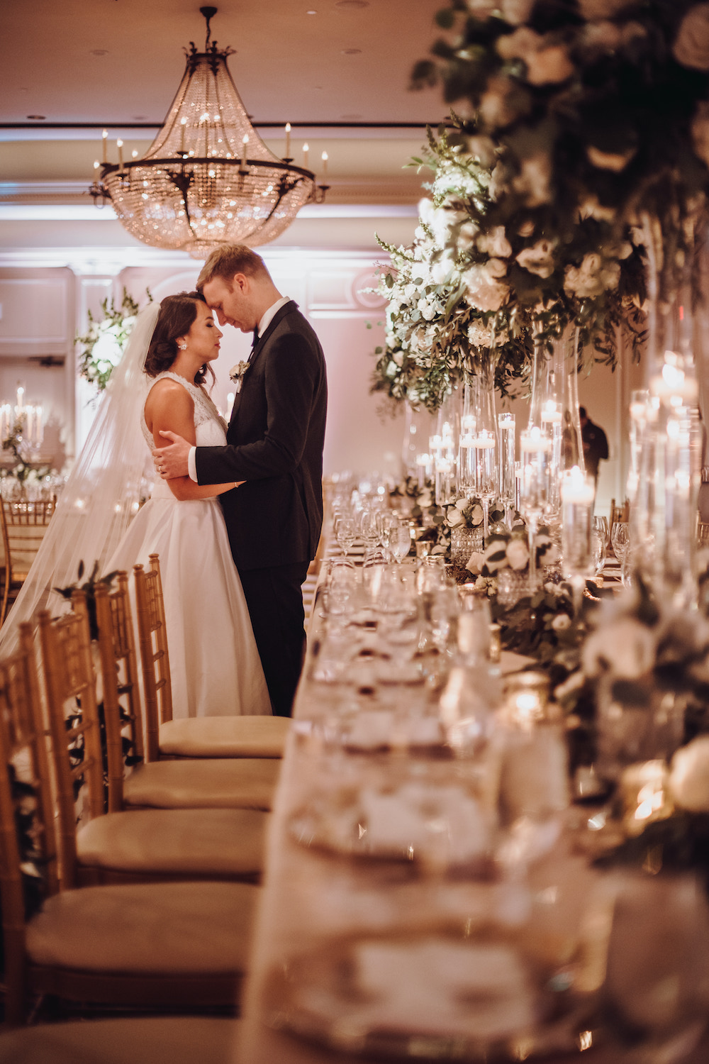Bride and groom holding each other at the end of long wedding table set with multiple tall blooming floral centerpieces, clear votive holders and strand of lush greenery inside the Houstonian Club and Space ballroom