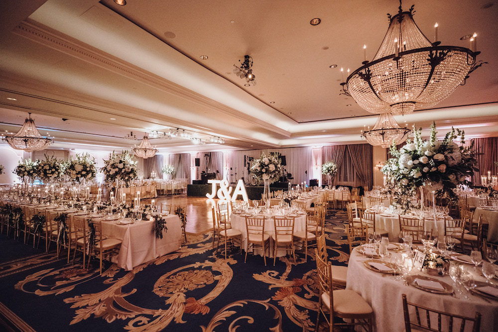 The Houstonian Hotel ballroom decorated for reception with long wedding table adorned with cascading floral centerpieces and round tables with gold chivari chairs and tall blooming white floral centerpieces.
