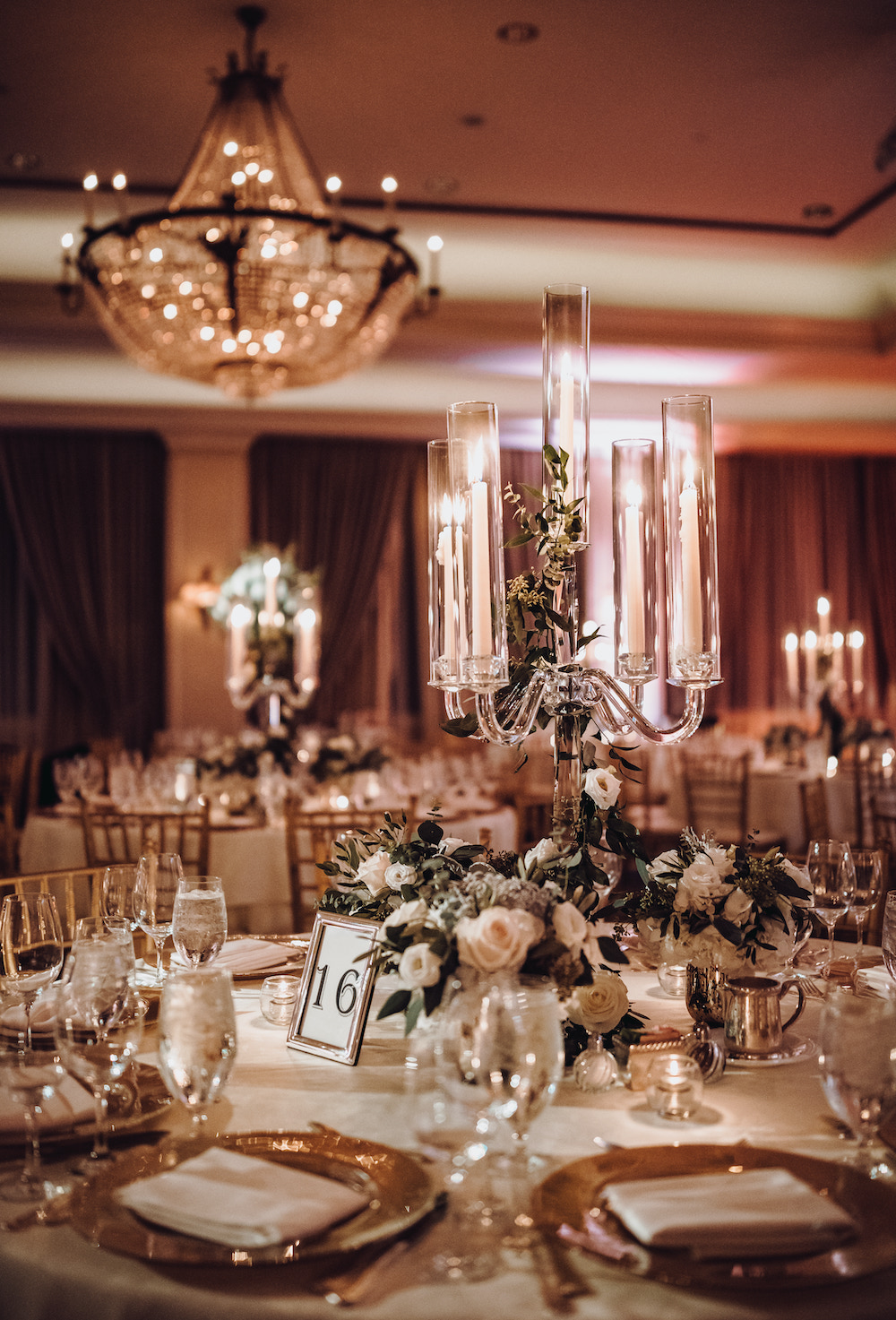 Table setting with small blush rose floral centerpiece, tall glass candelabras and gold chargers in the ballroom of the Houstonian Hotel Club & Spa.