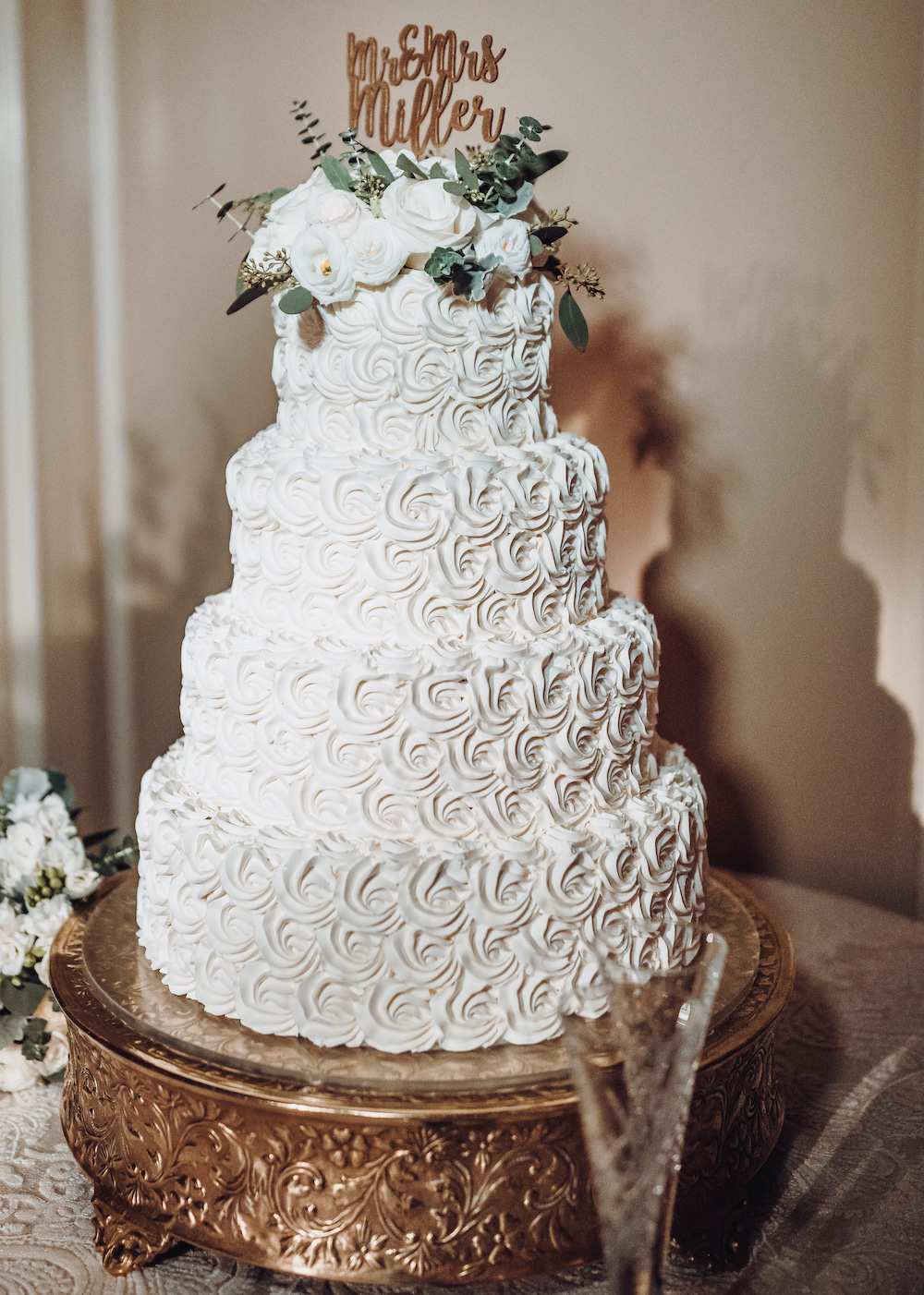 """Four tiered white wedding cake by Susie's Cakes with small rose inspired swirls in icing, topped with white roses, eucalyptus and gold lettering which reads, """"Mr. and Mrs. Miller"""""""