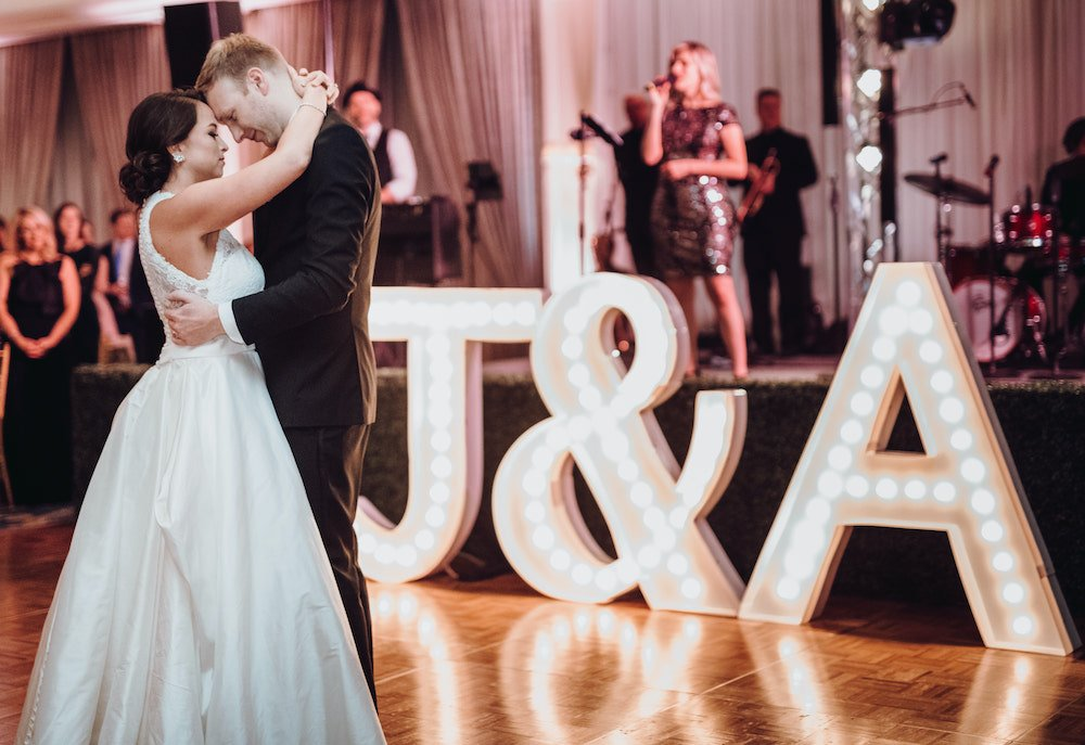 """Bride, in white gown with lace back and low updo, dancing with groom, in all black tuxedo, on light wood dance floor with tall lit marquee letters which reads, """"J&A"""""""