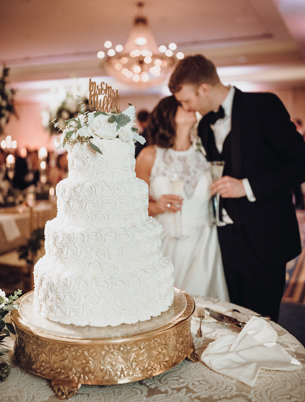 """White four tier cake with white blooms and custom lettering as topper which reads, """"Mr. and Mrs. Miller"""" and bride and groom in background kissing and holding champagne flutes"""
