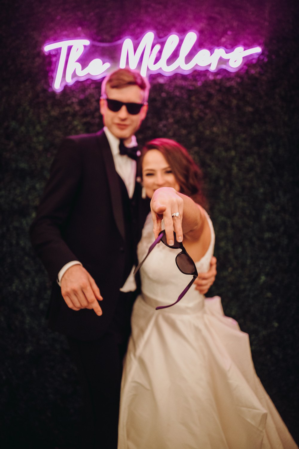 """Groom, wearing sunglasses and bride pointing to camera with sun glasses in hand, in front of greenery statement wall with fuchsia colored LED sign that reads, """"The Millers"""""""