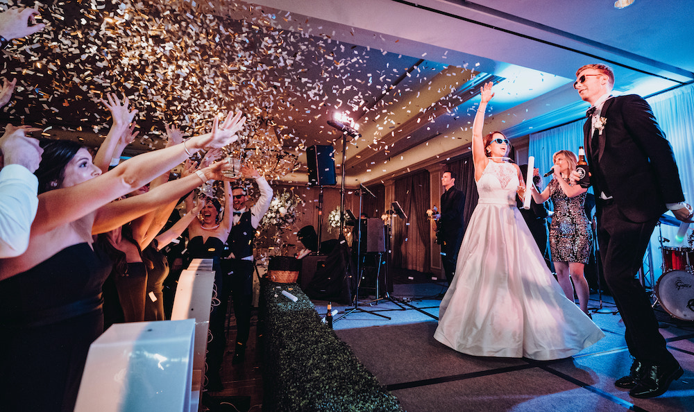 Gold confetti raining down on guests as bride and groom dance on stage with wedding entertainment group.