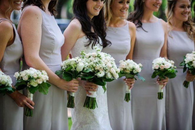 Bridesmaids white rose floral bouquets.