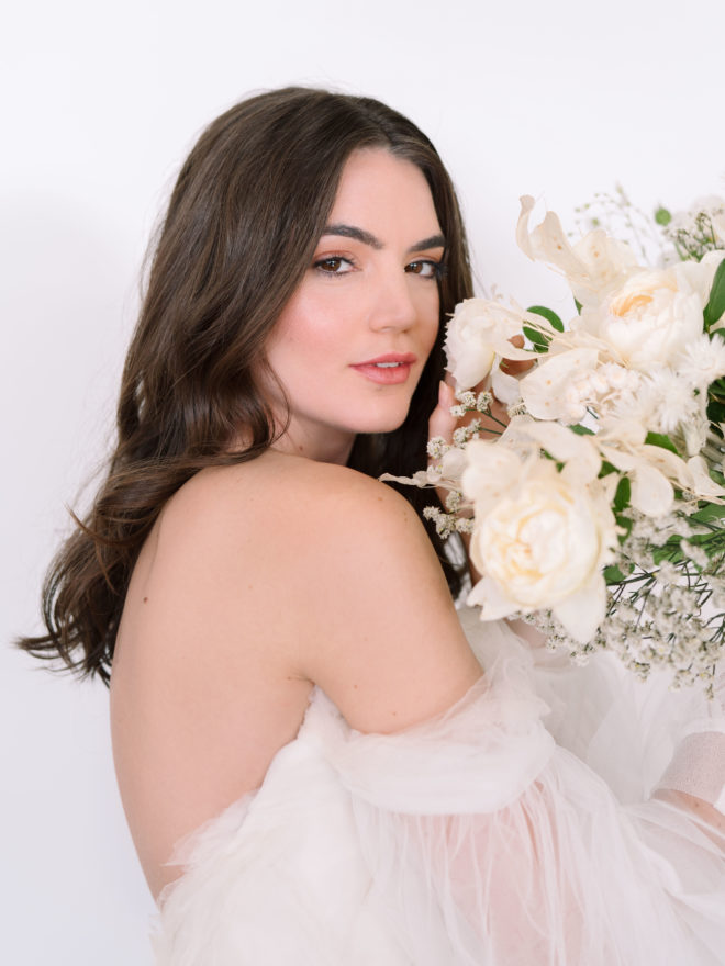 Bride with loosely curled hair, nude makeup and off the shoulder layered white gown holding white monochromatic bouquet of florals