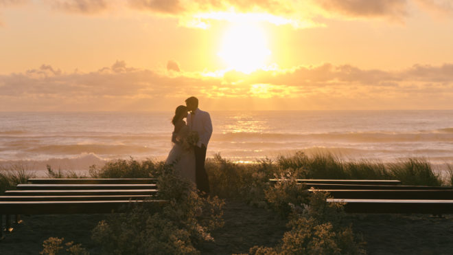 The bride and groom stand at the end of the wedding aisle with the sun setting over the Pacific ocean in the background after this Oregon destination wedding.