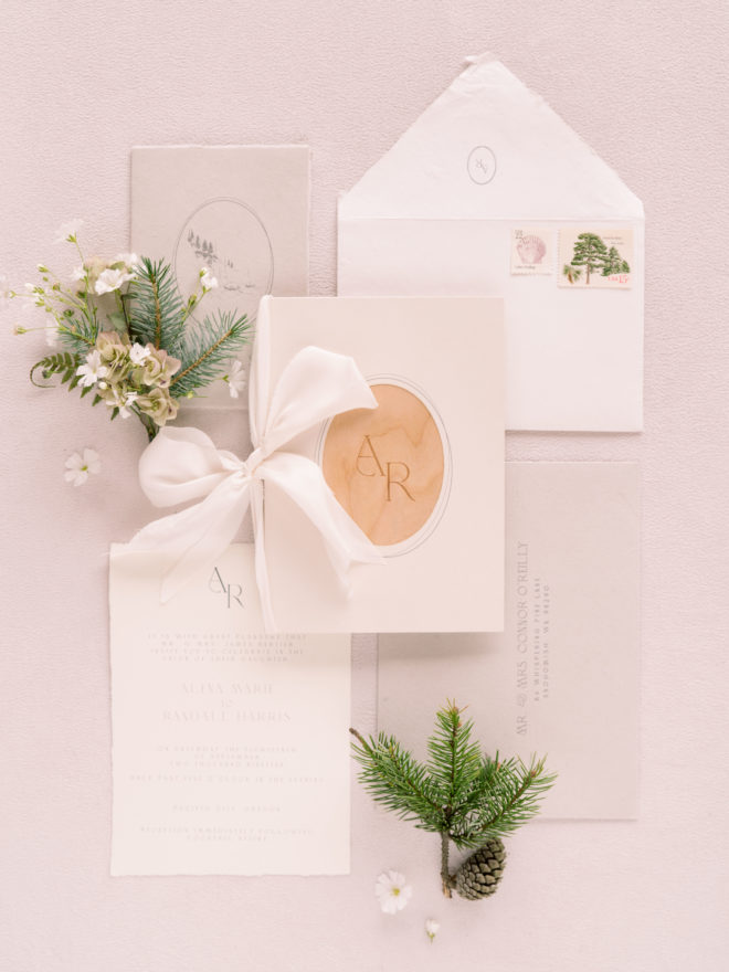 Minimalist wedding invitation with pops of natural wood and spruce sprig and floral boutonnière.