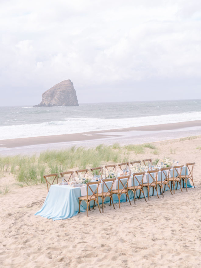 A lone, long wedding reception table with a flowy blue tablecloth sits on Cannon Beach.