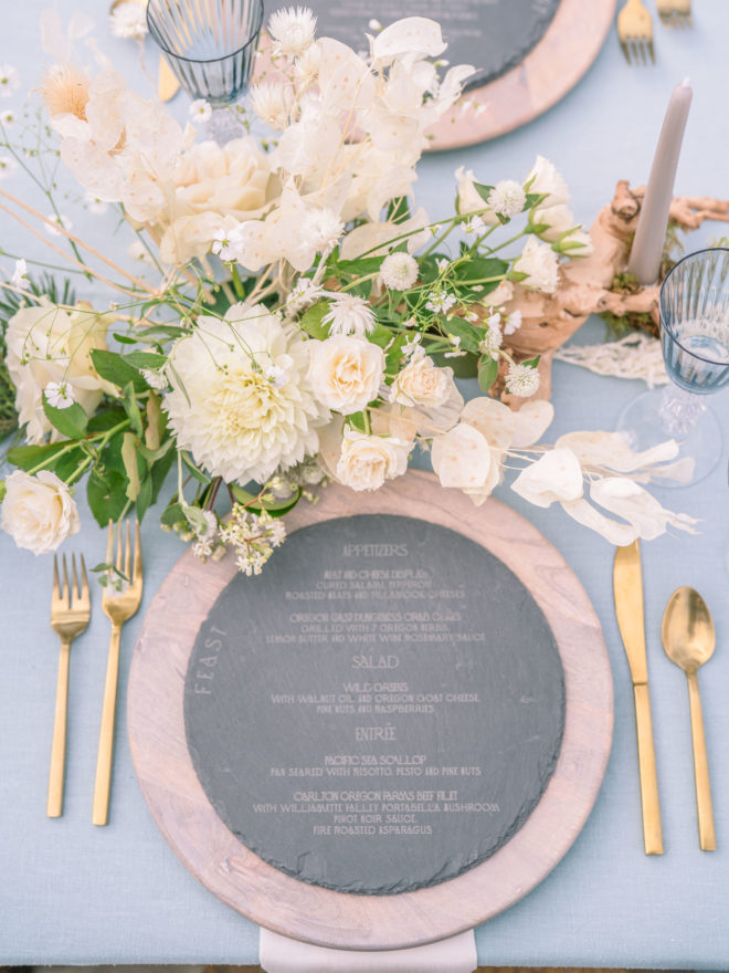 The wedding table setting for this Oregon Coast destination wedding includes wooden chargers, an engraved slate menu, gold flatware, and white flowers.