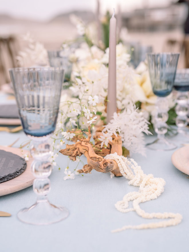 Blue glassware, candles, and driftwood elements accent white flowers on this wedding tablescape on Cannon Beach in Oregon.