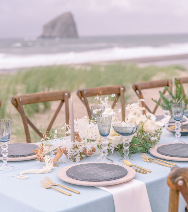 Al fresco tablescape on Cannon Beach- place settings in shades of blue and blush with vintage inspired blue glassware, blush chargers and light grey stone menus.