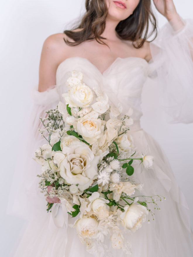 Bride wearing white off the shoulder tulle gown holding cascading bouquet of white and cream monochromatic florals, baby's breath and green botanicals.