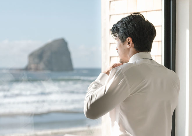 Groom putting his tie before the wedding ceremony, looking out window at Cannon Beach in Oregon