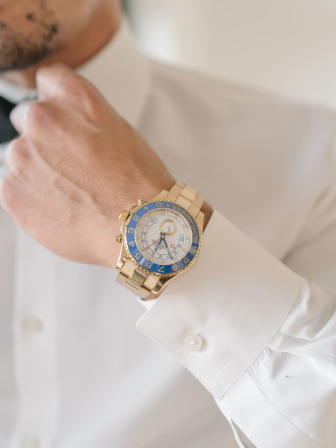 Groom adjusting black bow tie wearing gold wrist watch with a blue and white face and gold numbering.