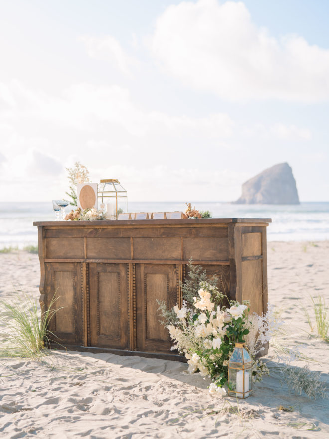 Rustic, wooden wedding escort table with white wedding flowers, gold accents, and Haystack Rock in the background.