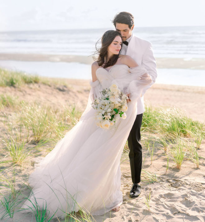 Bride, wearing off the shoulder white tulle gown holding white monochromatic bouquet, held from behind by a groom wearing a white tuxedo shirt, black bowtie and black pants on Oregon's Cannon Beach.