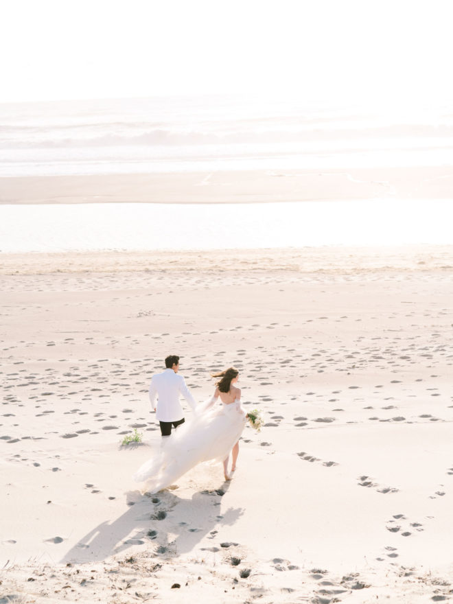 Ariel shot of Groom in white tuxedo jacket and black pants holding hands with bride in flowing white tulle gown on sun dappled Oregon Cannon beach