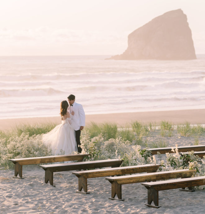 Bride and groom standing at end of al fresco wedding aisle amidst tall green beach botanicals with crashing waves and large rock formation behind them on Oregons Canon Beach