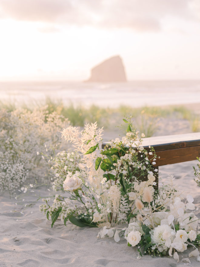 A white wedding floral arrangement sits next to a backless wooden bench at sunset on the beach in Oregon with Haystack Rock in the background.