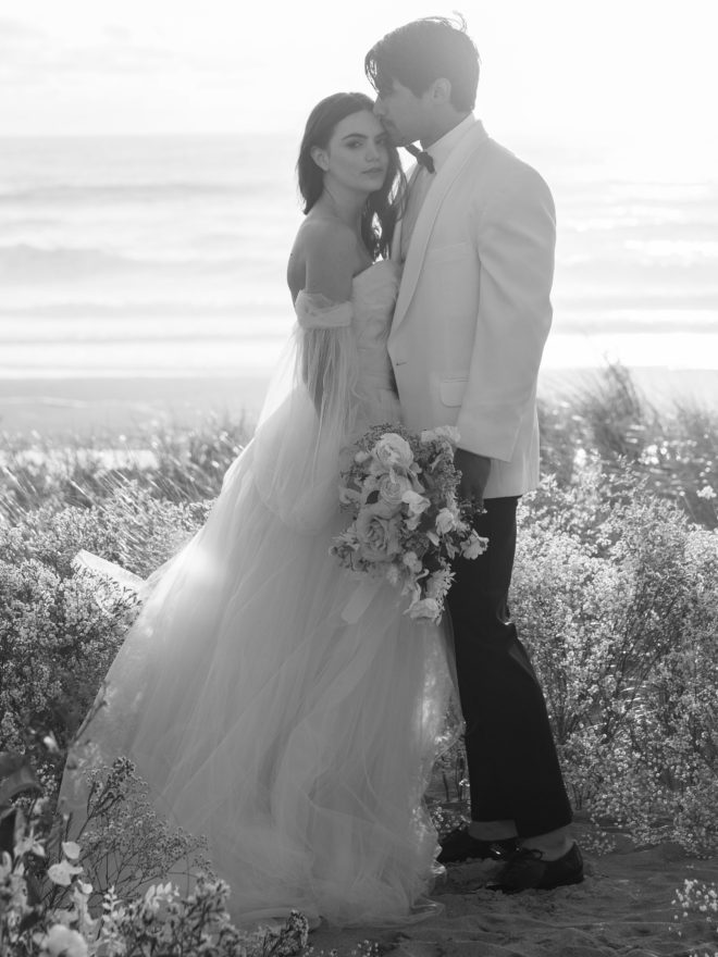 Black and white photo of bride, wearing tulle off the shoulder flowing gown holding bouquet of florals, looking directly at camera while groom, wearing white tuxedo jacket and black pants, kisses her forehead amidst beach botanicals on Cannon Beach.