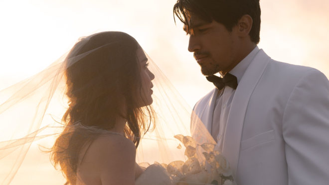 The model newlyweds gaze into each others eyes after the beach wedding as the sun sets behind them.