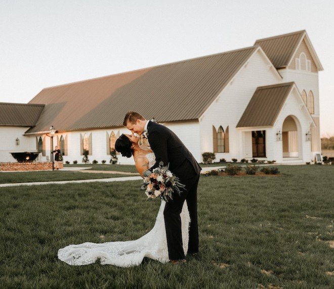 Bride and groom kissing in front of Deep In The Heart wedding venue.
