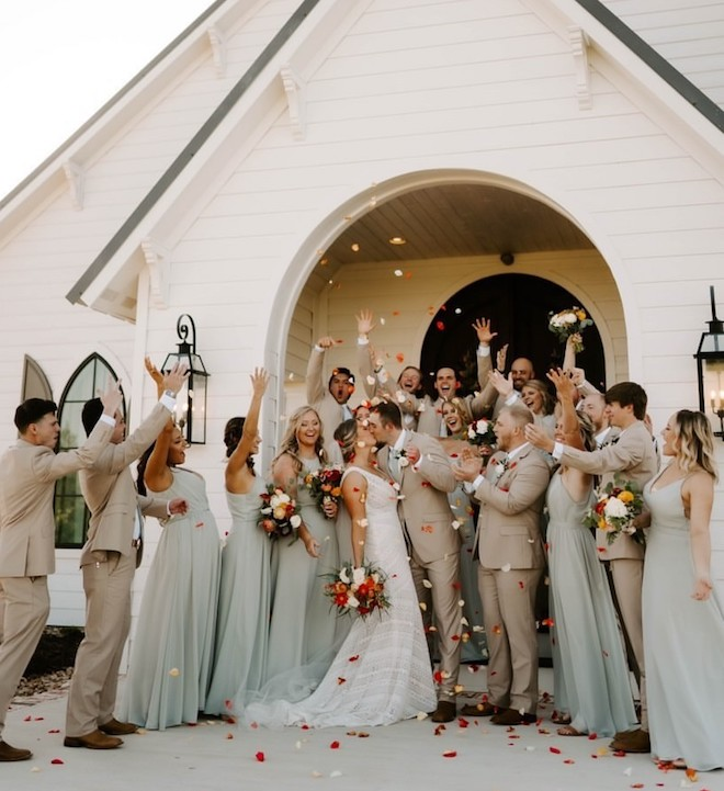 Bridesmaides and Groomsmen in sage and tan throwing flower petals around a bride and groom kissing.