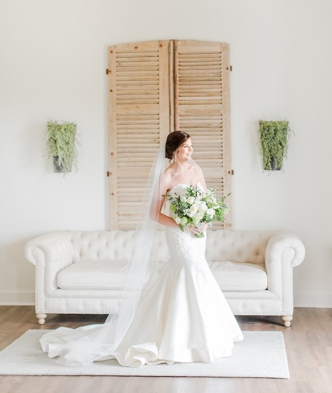 Bride in strappless white gown with train and veil holding green and white bouquet.