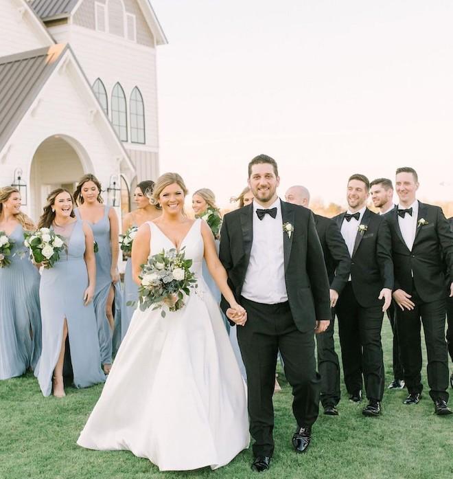 Bride and groom walking in front of bridesmaids in blue and groomsmen in black.