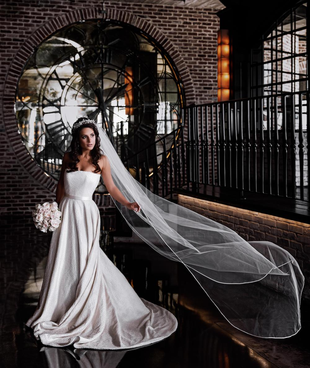 The bride's veil flows elegantly as she poses holding her wedding bouquet at The Astorian.