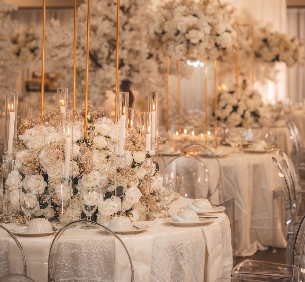 Large white floral arrangement with blush baby's breath and a gold pedestal above, surrounded by acrylic chairs atop white linens by Mod Effect Events.