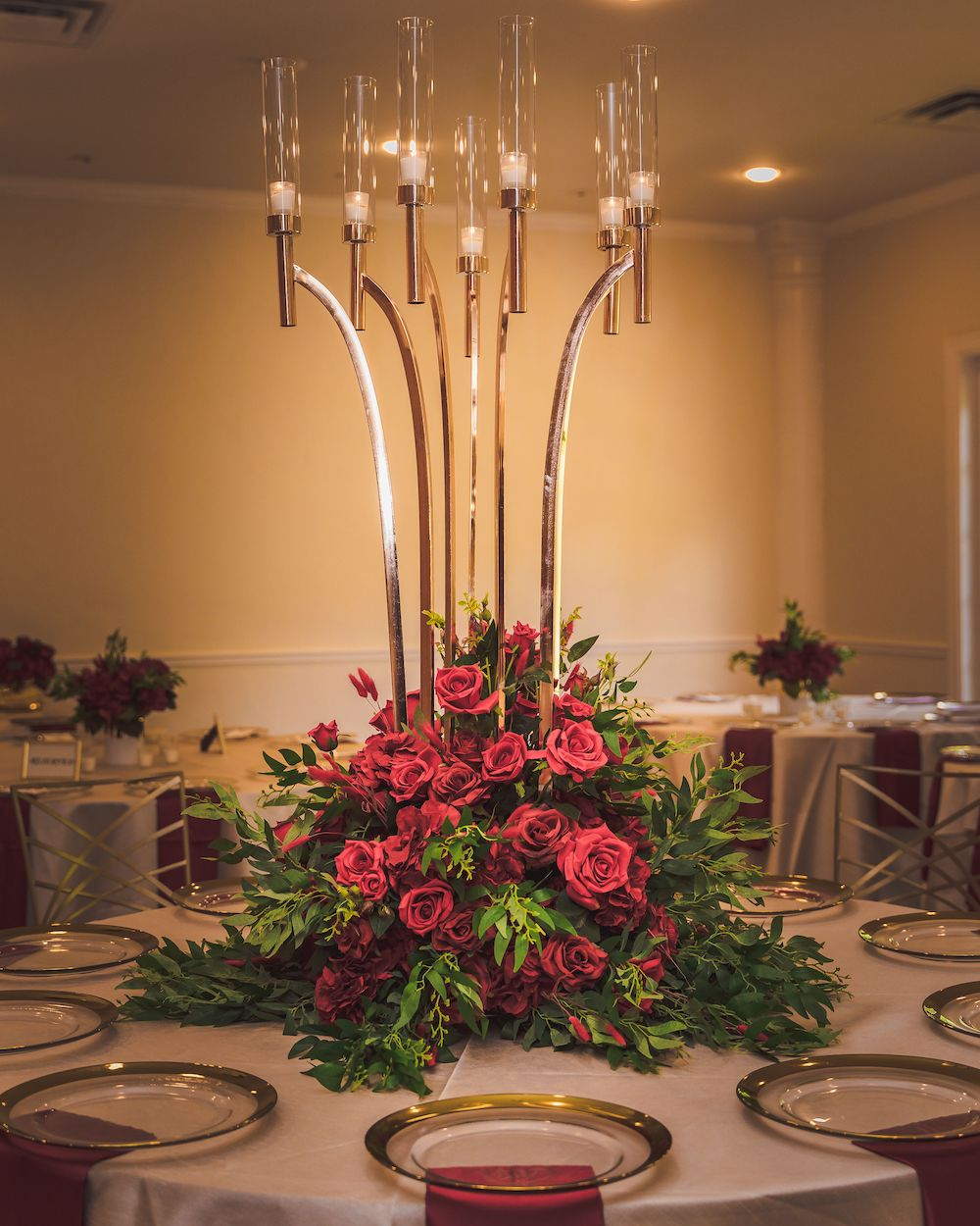 Tall gold and glass candle holders above a centerpiece arrangement of red roses.