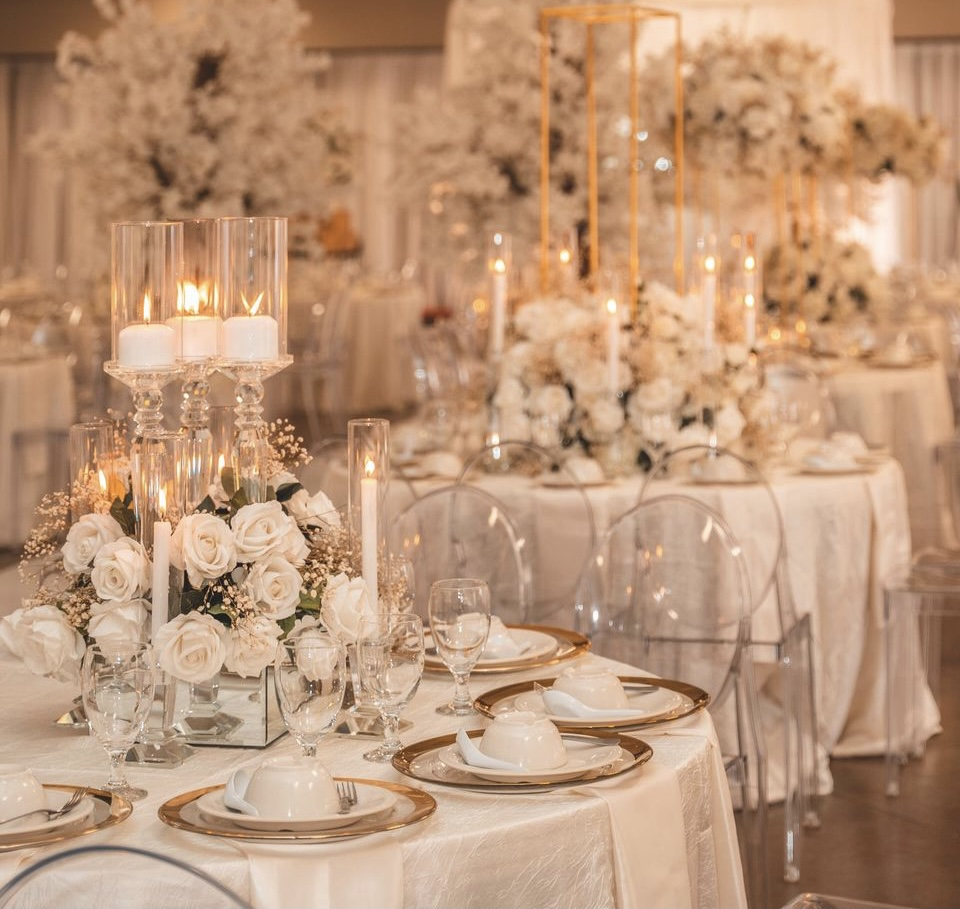 White wedding reception dinner with glass candle holders and pillar candles.