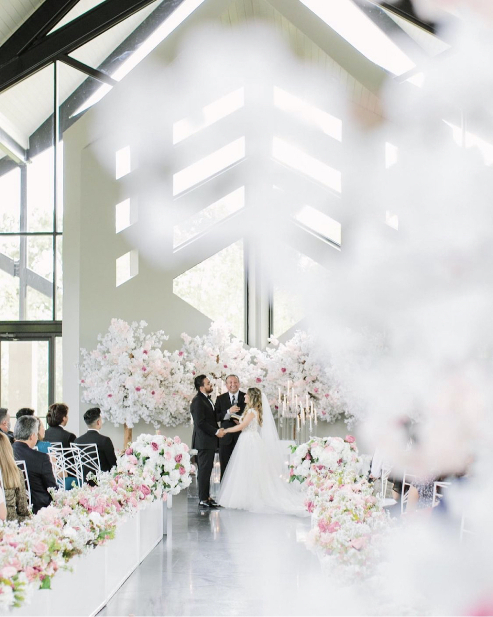 Interior shot of ceremony with lush pink and white florals by event designer, Mod Effect Events.
