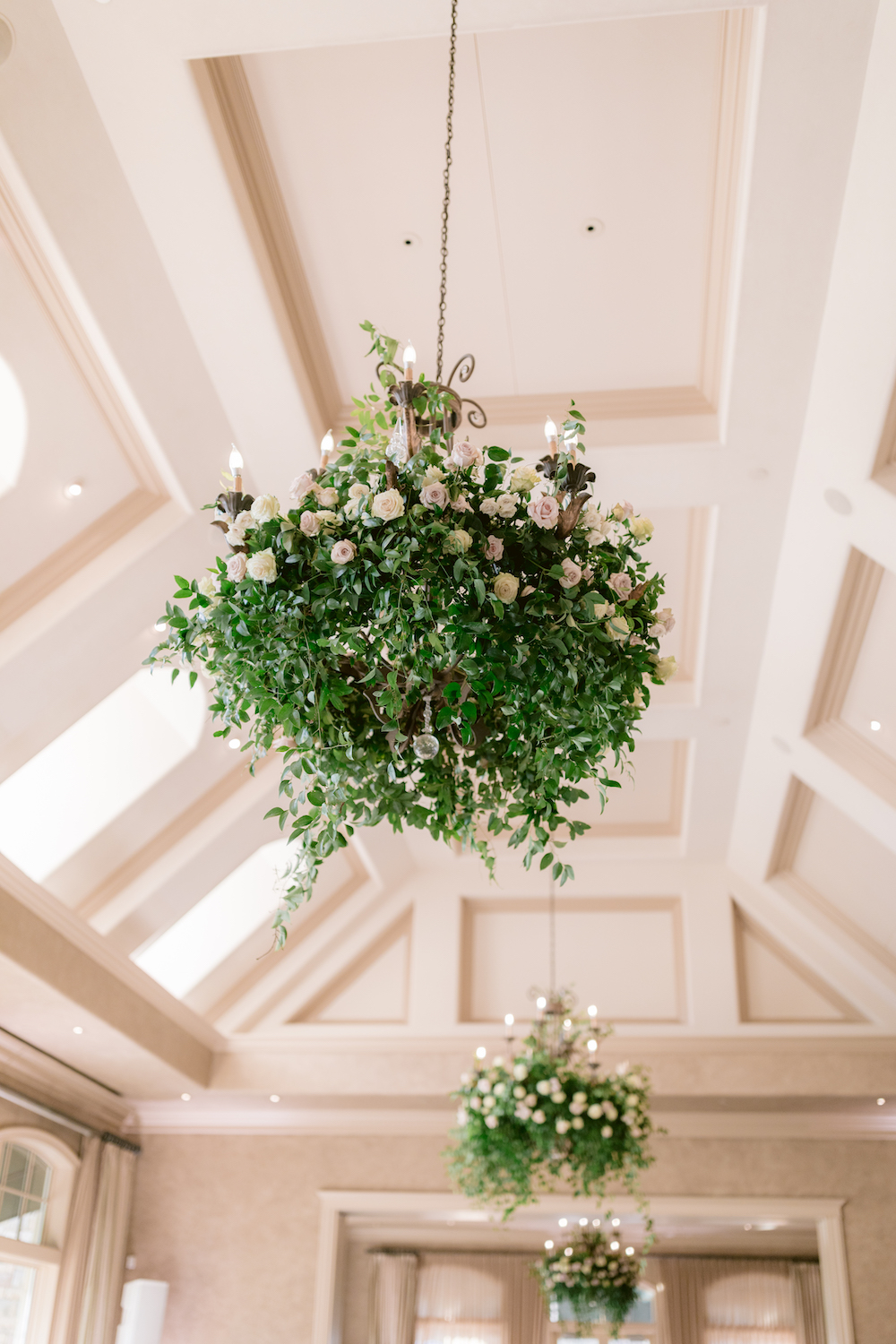 Hanging rose bush chandeliers with vines for an ethereal reception decor look.