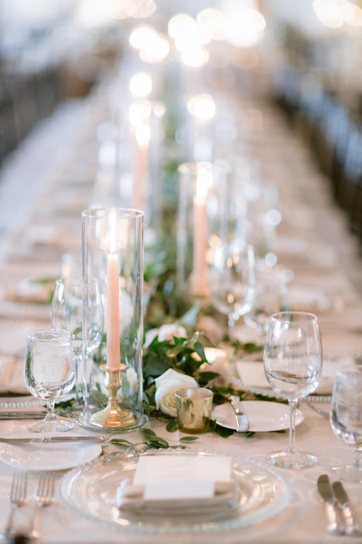 Elegant blush wedding reception table decor including ivory slim tapered candles in long cylinder vases.