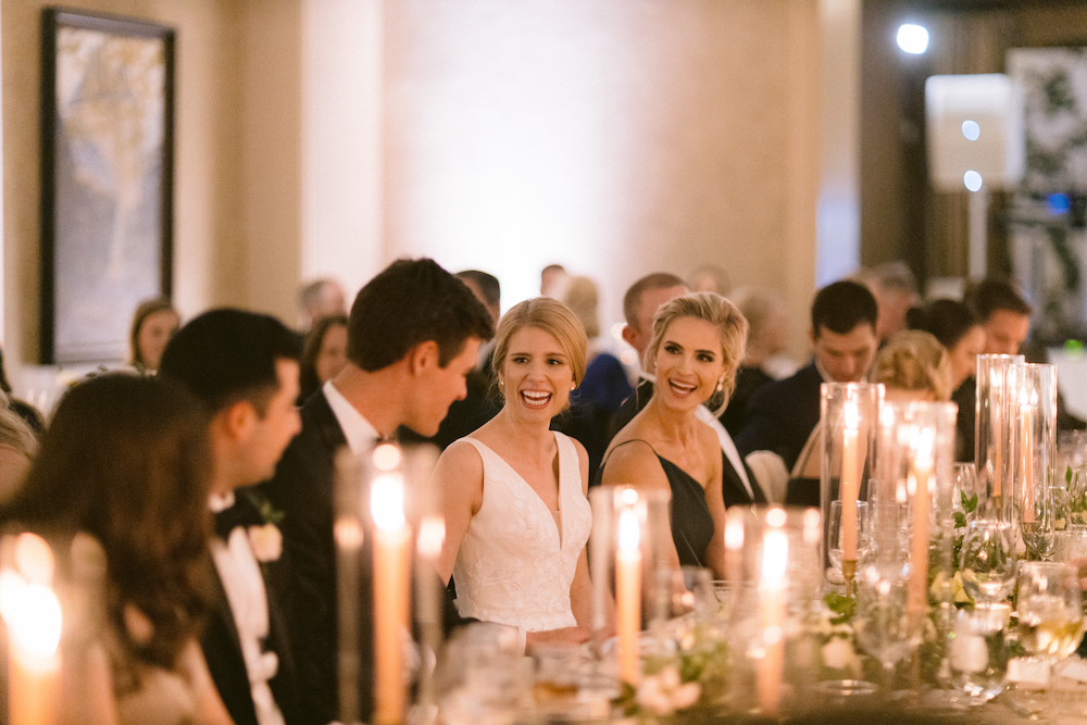 Bride smiling directly at the groom at a long reception table adorned with tall lit candles and a greenery runner in the ballroom of Royal Oaks Country Club.