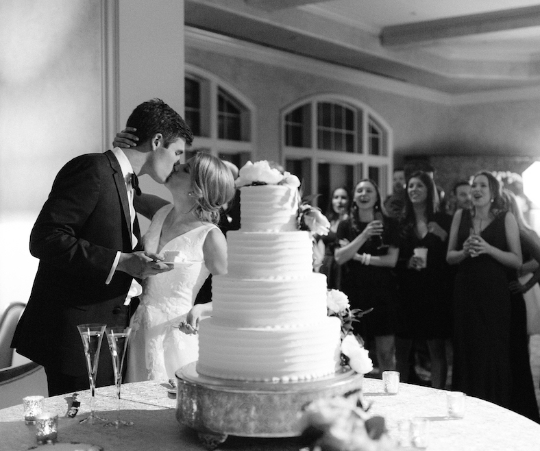 Bride and groom share kiss while cutting their buttercream cake by Susie's cake in Houston.