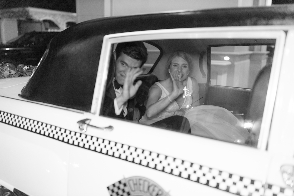 Bride and groom ride in a white and checkered getaway car provided by Royal Oaks Country Club.