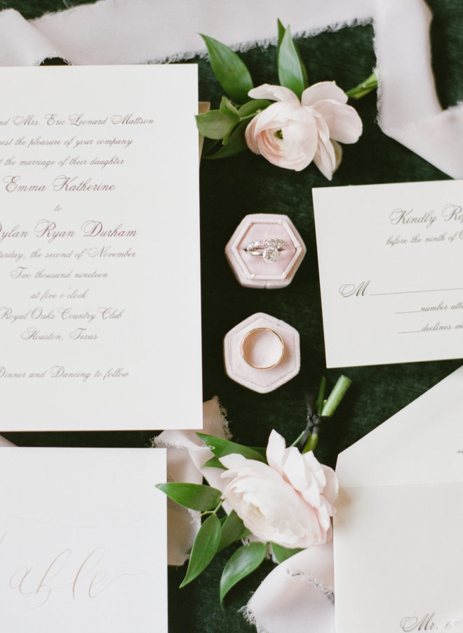 Flay lay of white invitation suite with cursive lettering, two blush rose blossoms and the couple's wedding rings atop pink ring boxes.