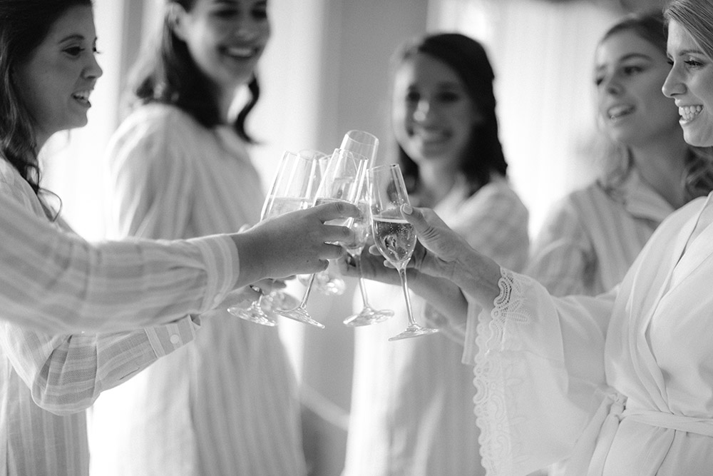 Bride, in white robe, and bridesmaids, in matching striped robes, toast with filled champagne flutes.