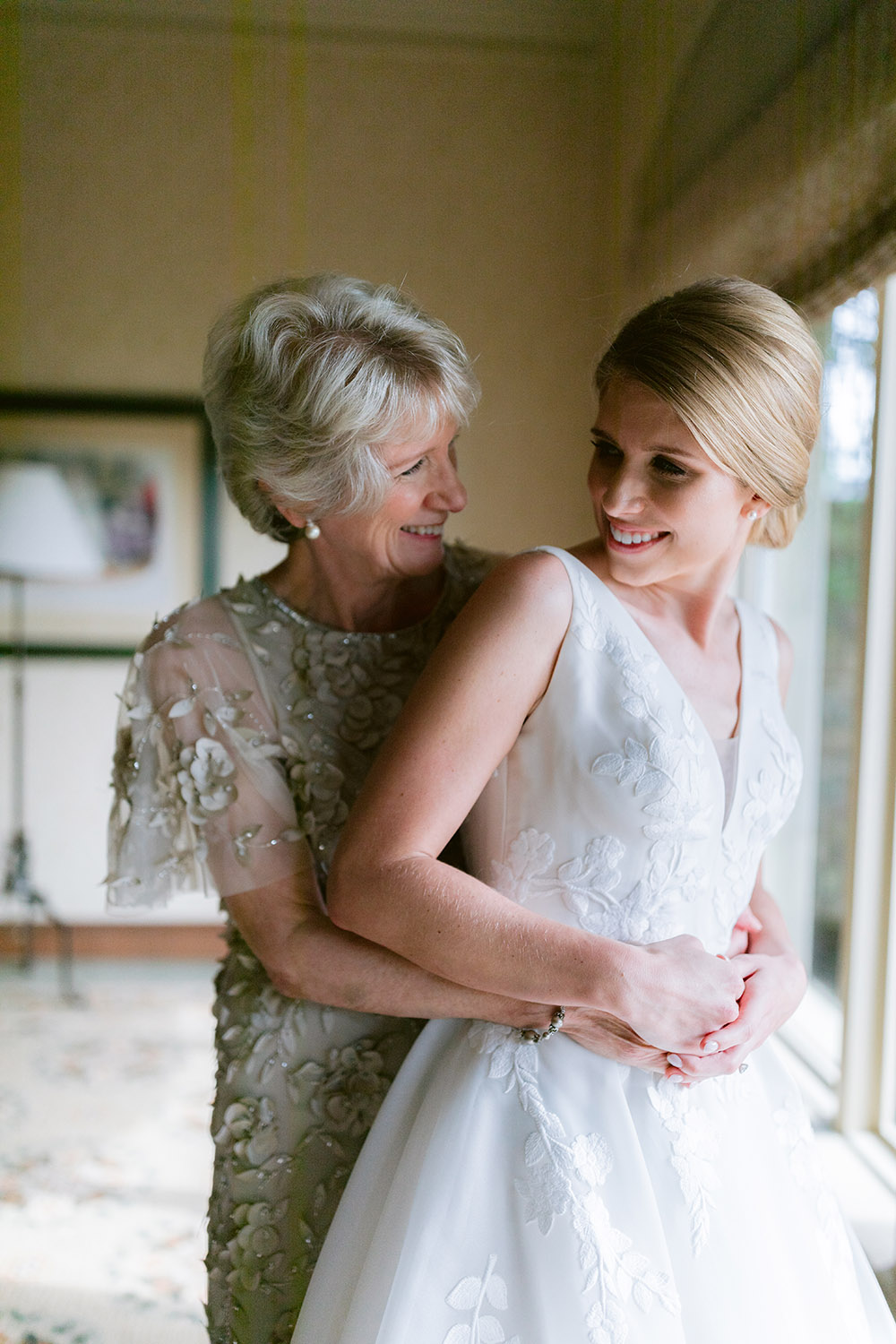 Mother of the bride and bride smiling at each other in a sunny interior space at Royal Oaks Country Club.
