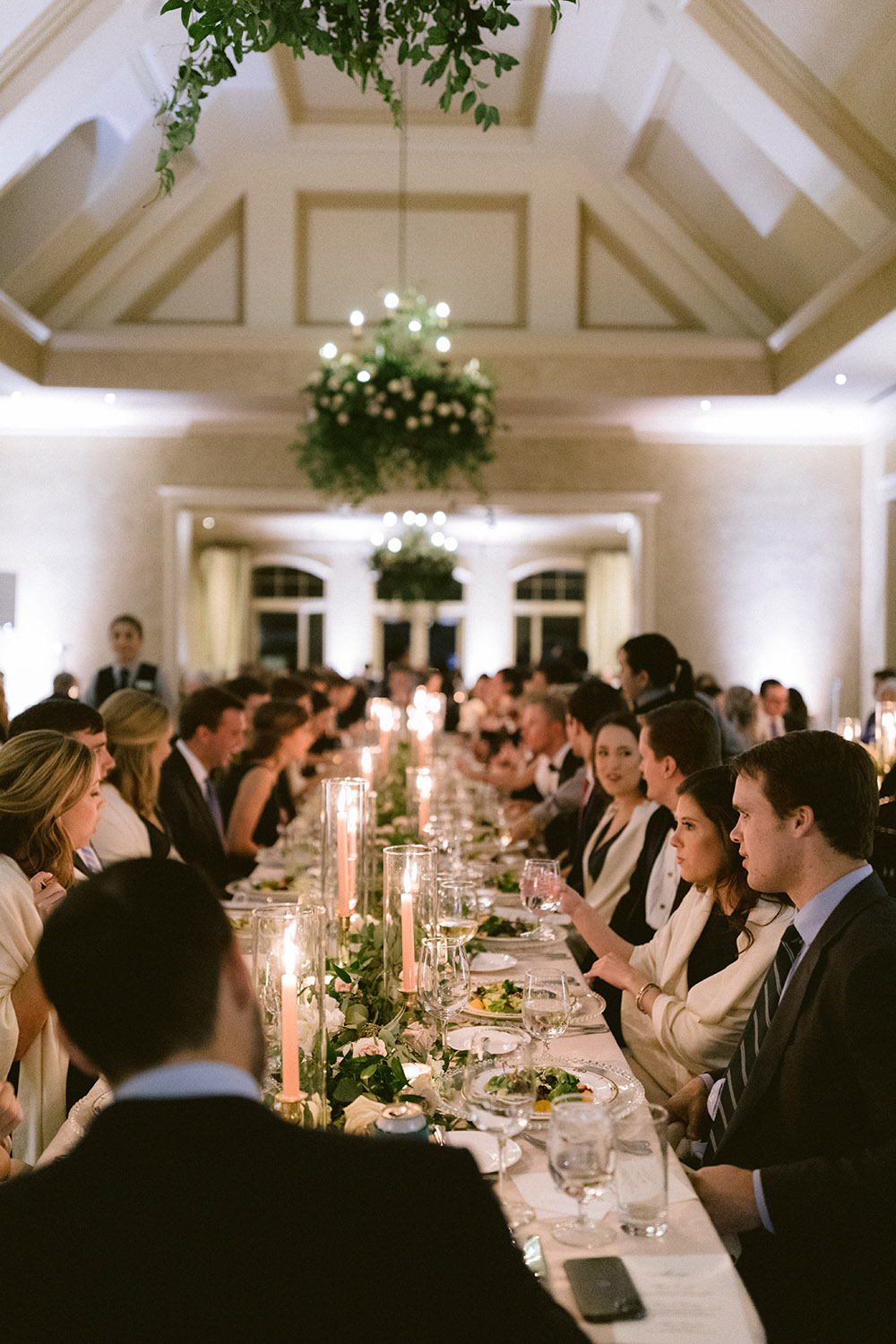 Guests seated at a long reception table, adorned with tall pink glowing candles and greenery.